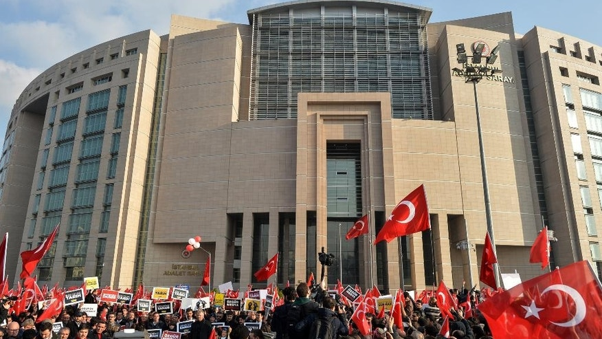 People wave national flags outside a courthouse before the release of Ekrem Dumanli, editor-in-chief of Zaman newspaper, in Istanbul, Turkey, Friday, Dec. 19, 2014. A local court ordered the release of Dumanli six days after his detention. Police conducted raids in a dozen Turkish cities Sunday, detaining 32 people — including journalists, TV producers and police — known to be close to a movement led by a U.S.-based moderate Islamic cleric who is a strong critic of President Recep Tayyip Erdogan. It was the latest crackdown on cleric Fethullah Gulen's movement, which the government has accused of orchestrating an alleged plot to try to bring it down. (AP Photo)