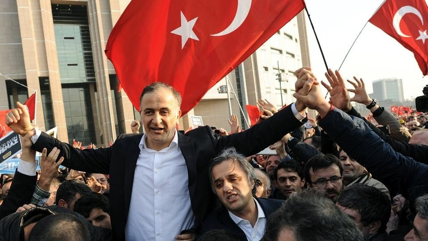 Ekrem Dumanli, editor-in-chief of Zaman newspaper, salutes cheering supporters outside a courthouse after his release in Istanbul, Turkey, Friday, Dec. 19, 2014. A local court ordered the release of Dumanli six days after his detention. Police conducted raids in a dozen Turkish cities Sunday, detaining 32 people — including journalists, TV producers and police — known to be close to a movement led by a U.S.-based moderate Islamic cleric who is a strong critic of President Recep Tayyip Erdogan. It was the latest crackdown on cleric Fethullah Gulen's movement, which the government has accused of orchestrating an alleged plot to try to bring it down. (AP Photo)