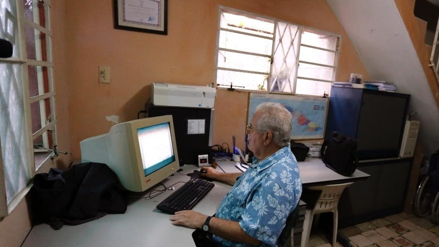 Cuban dissident Elizardo Sanchez Santa Cruz-Pacheco, president of the Cuban Human Rights and National Reconciliation Commission, works on his computer at home in Havana, Cuba, Friday, Dec. 19, 2014. Sanchez, one of the only independent human rights activists tolerated on the island, said he's been getting calls from inmates asking him if he has a list and whether they're on it, but he's had to say he doesn't know. There's been no evidence of any mass release, he said. (AP Photo/Desmond Boylan)