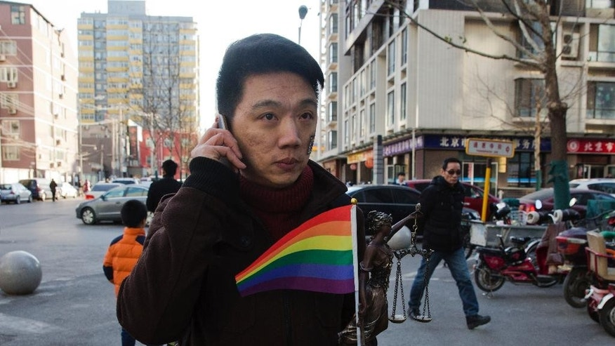 Yang Teng holds up a statue depicting a goddess of justice and a rainbow color flag as he arrives to attend a court verdict in Beijing, China, Friday, Dec. 19, 2014.  A Chinese psychological clinic was ordered Friday to pay compensation to Yang who is gay and sued it for administering electric shocks intended to make him heterosexual, in what is believed to be China's first case involving so-called conversion therapy. (AP Photo/Ng Han Guan)