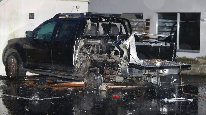 The remains of a car which was damaged in an explosion early Saturday morning Dec. 20, 2014 in Malmo Sweden. Another minor bomb wrecked an entrance to a house in the same neighborhood of Rosengard, Malmo. No one was injured by the explosions. (AP photo/TT News Agency, Stig-Ake Jonsson)    SWEDEN OUT