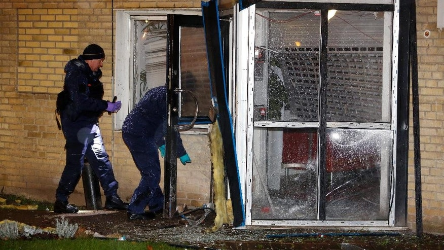 Police investigate a building after the entrance was blown up early Saturday morning Dec. 20, 2014 in Malmo Sweden. Another minor bomb wrecked a car in the same neighborhood of Rosengard, in Malmo. No one was injured by the explosions. (AP photo/TT News Agency, Stig-Ake Jonsson)    SWEDEN OUT