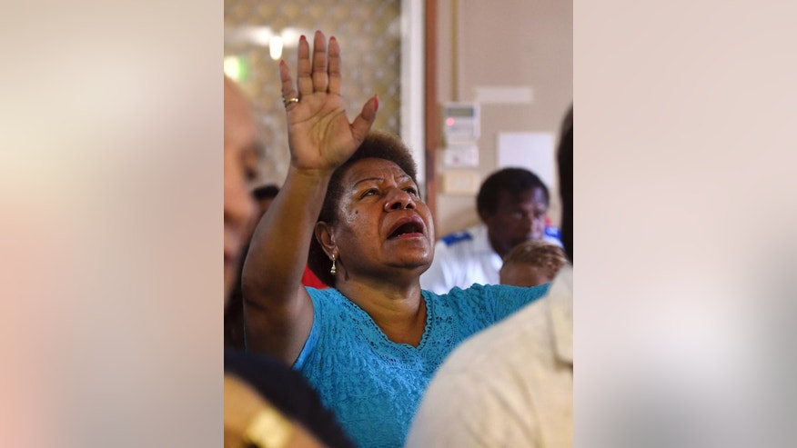 A woman prays during a church service to remember eight children who were killed in the Cairns suburb of Manoora, Australia, Sunday, Dec. 21, 2014. Mersane Warria, 37, was charged with eight counts of murder in a bedside hearing at a hospital in the northern city of Cairns where she is recovering from stab wounds, Queensland state police said. (AP Photo/Dan Peled/Pool)