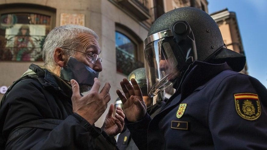 A policeman communicates with a demonstrator by a cordoned off street,  during a protest against Spanish Citizens Security Law in Madrid, Spain, Saturday, Dec. 20, 2014. Thousands of people have gathered in several Spanish cities to protest against a new law that sets hefty fines for offenses such as burning the national flag and holding demonstrations outside parliament buildings or strategic installations. Also can be fined protesters who prevent authorities from carrying out evictions, insulting a police officer and disseminating photographs of police officers that endanger them or police operations. The legislation also allows for the summary expulsion of migrants entering the country's North African enclaves illegally. (AP Photo/Andres Kudacki)