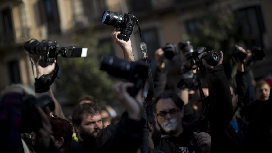 Photographers raise their cameras in front of police officers during a protest against Spanish Citizens Security Law in Barcelona, Spain, Saturday, Dec. 20, 2014. Thousands of people have gathered in several Spanish cities to protest against a new law that sets hefty fines for offenses such as burning the national flag and holding demonstrations outside parliament buildings or strategic installations. (AP Photo/Emilio Morenatti)
