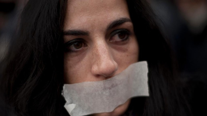 "Terexe Lopez, 33 years old,  covers her mouth during a protest against Spanish Citizens Security Law, in Bilbao, northern Spain, Saturday, Dec. 20, 2014. Today citizens protested in Spain against the Citizen Security Law that was approved by the Government alone last December the 11th. Civil rights collectives (more than 80) were demonstrated in Spain against the ""Gag Law"", because they believe the law limits fundamental rights. (AP Photo/Alvaro Barrientos)"