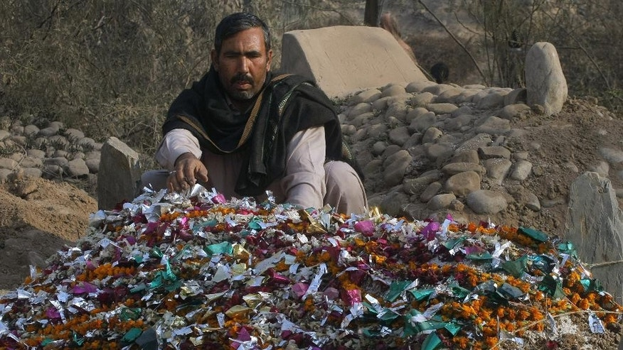 In this Saturday, Dec. 20, 2014 photo, Pakistani gravedigger Taj Muhammad adjusts wreaths on a grave at the Rahman Baba graveyard in Peshawar, Pakistan. Muhammad, one of the gravediggers at Peshawar's largest graveyard, has a rule. He said he never cries when he buries the dead. He's a professional, he said. But as the dead bodies, mostly children, started coming in from a school massacre this week that killed 148 people, he began to weep. (AP Photo/Mohammad Sajjad)