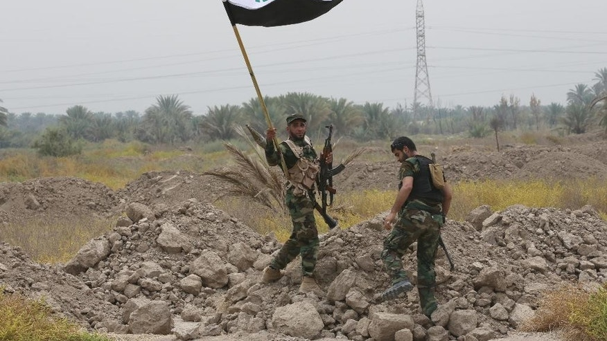 In this Monday, Aug 18, 2014 file photo, Iraqi Shiite fighters make their way to the front line to fight militants from the extremist Islamic State group in Jurf al-Sakhar, 43 miles (70 kilometers) south of Baghdad, Iraq. The Shiite fighters are credited for curbing the Sunni militants advance on Baghdad and the surrounding areas and for achieving significant progress on the ground, including breaking the extremists' siege on the northern Shiite-majority town of Amerli in August and later, in operations to liberate Jurf al-Sakher, a town south of Baghdad. (AP Photo/Hadi Mizban, File)