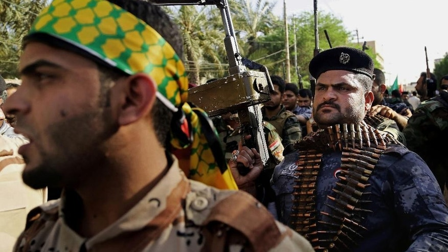 FILE - In this Monday, June 16, 2014 file photo, Shiite tribal fighters raise their weapons and chant slogans against the al-Qaida-inspired Islamic State of Iraq and the Levant (ISIL), now called the Islamic State group,  in Basra, Iraq's second-largest city, 340 miles (550 kilometers) southeast of Baghdad, Iraq. The Shiite fighters are credited for curbing the Sunni militants advance on Baghdad and the surrounding areas and for achieving significant progress on the ground, including breaking the extremists' siege on the northern Shiite-majority town of Amerli in August and later, in operations to liberate Jurf al-Sakher, a town south of Baghdad. (AP Photo/Nabil Al-Jurani, File)
