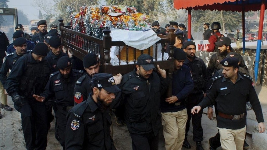 Pakistani police officers carry the casket of their fellow officer killed in the gunbattle with militants, during the funeral procession in Peshawar, Pakistan, Saturday, Dec. 20, 2014. A security official and a police officer were killed during a shootout with militants in Peshawar, police officer Ijaz Ahmed said. He said two militants were killed. (AP Photo/Mohammad Sajjad)
