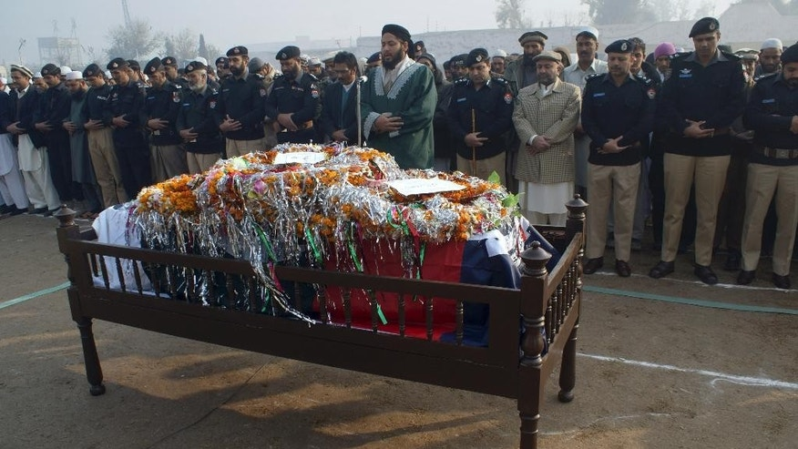 Pakistani police officers offer prayers for their fellow officer who was killed in gunbattle with militants, during the funeral procession in Peshawar, Pakistan, Saturday, Dec. 20, 2014. A security official and a police officer were killed during a shootout with militants in Peshawar, police officer Ijaz Ahmed said. He said two militants were killed. (AP Photo/Mohammad Sajjad)