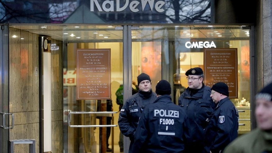 Police officers stand in front of the 'KaDeWe' (Kaufhaus des Westens) department store in Berlin, Germany, Saturday, Dec. 20, 2014. Police say robbers struck at Berlin's famous KaDeWe, smashing display cases and running off with their loot. Police spokeswoman Heidi Vogt said the luxury department store on Kurfuerstendamm avenue was robbed by four men Saturday morning soon after it opened. (AP Photo/Michael Sohn)