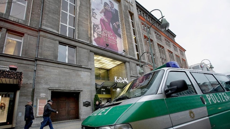 A police car stands in front of the 'KaDeWe' (Kaufhaus des Westens) department store in Berlin, Germany, Saturday, Dec. 20, 2014. Police say robbers struck at Berlin's famous KaDeWe, smashing display cases and running off with their loot. Police spokeswoman Heidi Vogt said the luxury department store on Kurfuerstendamm avenue was robbed by four men Saturday morning soon after it opened. (AP Photo/Michael Sohn)
