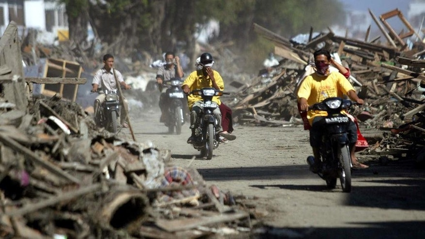 In this Thursday, Dec. 30, 2004 photo, motorists ride through debris on a street in Banda Aceh, Aceh province, Indonesia. Ten years after that gigantic wave swept into this city of 4 million on the day after Christmas, Banda Aceh has been almost totally restored. The tangled mountains of rubbish are gone, and it's hard to imagine the destruction that once choked rivers, blocked streets and ripped up trees by the roots. (AP Photo/Dita Alangkara, File)