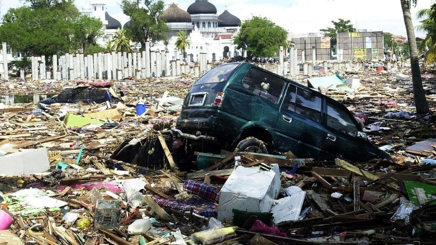 In this Monday, Dec. 27, 2004 file photo, debris litter the front lawn of Baiturrahman Grand Mosque in Banda Aceh, Aceh province, Indonesia. Ten years after that gigantic wave swept into this city of 4 million on the day after Christmas, Banda Aceh has been almost totally restored. The tangled mountains of rubbish are gone, and it's hard to imagine the destruction that once choked rivers, blocked streets and ripped up trees by the roots. (AP Photo/Achmad Ibrahim, File)