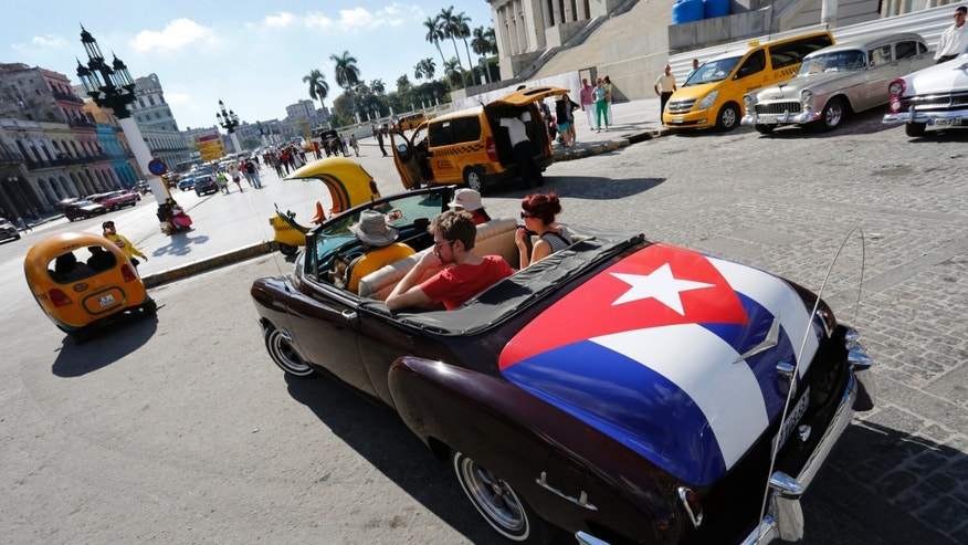 FILE - In this Dec. 18, 2014 file photo, tourists take a ride in a classic American convertible car with the Cuban national flag painted on the trunk, in Havana, Cuba. American businesses have begun imagining ways to capitalize on last weeks announcement that the United States will restore diplomatic ties with Cuba and ease curbs on trade with one of the last surviving communist regimes. The opening to Cuba could benefit, among others, U.S. farmers, auto and tractor makers, airline and hotel companies and telecom equipment makers. (AP Photo/Desmond Boylan, File)