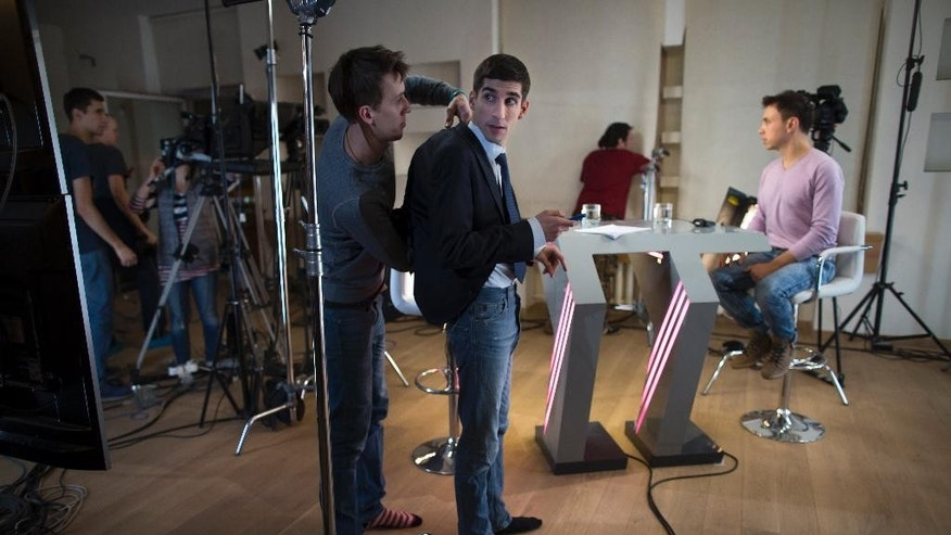 In this photo taken on Wednesday, Dec.  10, 2014, A camera assistant adjusts a microphone on Dozhd Channel's s anchorman Lev Parkhomenko, center, in their studio-apartment in Moscow, Russia .Russia's only independent TV channel, Dozhd, faced all sorts of pressure this year and while the government was careful not to shut it down, a Kremlin-instigated smear campaign is causing a slow demise of this rare independent broadcaster. (AP Photo/Alexander Zemlianichenko)