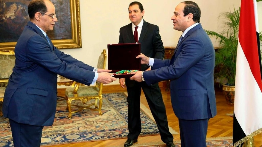 In this photo provided by Egypt's state news agency MENA, Egyptian President Abdel-Fattah el-Sissi, right, gives a medal and a badge for the Republic Award to intelligence chief Gen. Mohammed Farid el-Tohamy in Cairo, Egypt, Sunday, Dec. 21, 2014. El-Sissi awarded el-Tohamy one of the state's highest awards after ordering his retirement. (AP Photo/MENA, Mohammed Samaha)