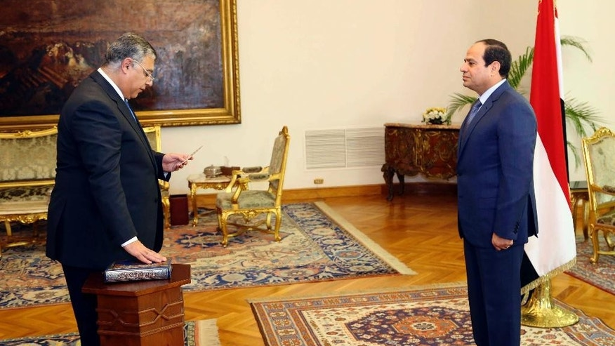 In this photo provided by Egypt's state news agency MENA, Egyptian President Abdel-Fattah el-Sissi, right, swears in Maj. Gen. Khaled Fawzy as acting intelligence chief in Cairo, Egypt, Sunday, Dec. 21, 2014. El-Sissi awarded intelligence chief Gen. Farid el-Tohamy the Republic Award, one of the state's highest awards, in his office Sunday after ordering his retirement. El-Sissi then swore in el-Tohamy's replacement, Fawzy, as acting intelligence chief. (AP Photo/MENA, Mohammed Samaha)