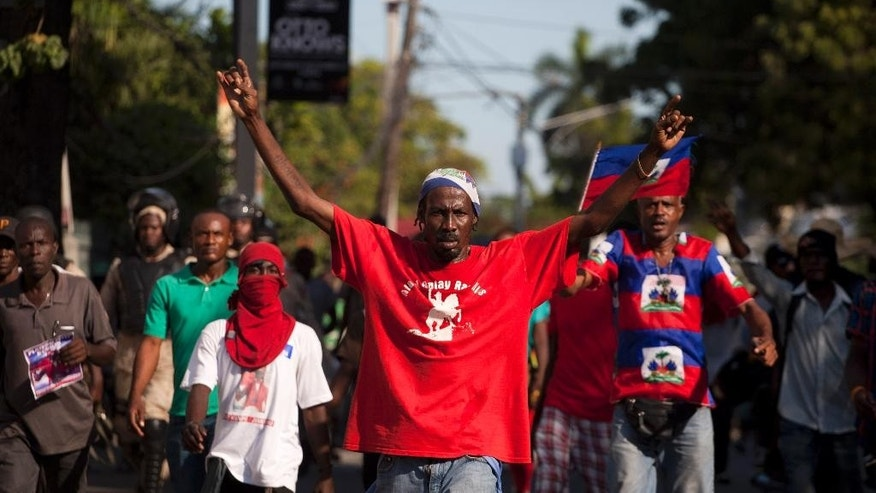 Anti-government demonstrators walk in the street during a protest calling for the resignation of Haiti's President Michel Martelly in Port-au-Prince, Haiti, Thursday, Dec. 18, 2014. President Martelly met Wednesday with opposition leaders in a bid to stabilize the politically fractious country as pressure mounted on him to appoint an interim prime minister. ( AP Photo/Dieu Nalio Chery)
