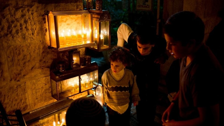 Jewish children watch their father light candles during the Jewish holiday of Hanukkah in the Jewish Quarter of the Old City in Jerusalem on Saturday, Dec. 20, 2014. The Jewish festival of light is an eight-day commemoration of the Jewish uprising in the second century B.C. against the Greek-Syrian kingdom, which had tried to put statues of Greek gods in the Jewish Temple in Jerusalem. (AP Photo/Dusan Vranic)
