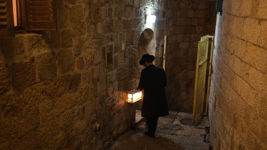 An ultra Orthodox Jew lights candles during the Jewish holiday of Hanukkah in the Jewish Quarter of the Old City in Jerusalem on Saturday, Dec. 20, 2014. The Jewish festival of light is an eight-day commemoration of the Jewish uprising in the second century B.C. against the Greek-Syrian kingdom, which had tried to put statues of Greek gods in the Jewish Temple in Jerusalem. (AP Photo/Dusan Vranic)