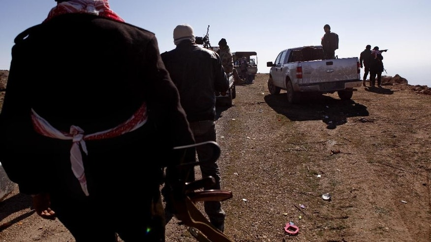 Iraqi Kurdish forces head to battle Islamic State militants, on the summit of Mount Sinjar, in Iraq, Sunday, Dec. 21, 2014. Iraqi Kurdish fighters pushed their way Sunday into the town of Sinjar, backed by U.S.-led coalition airstrikes against Islamic State militants who captured the town last summer. Loud explosions and intense gunbattles were heard from inside the town. (AP Photo/Dalton Bennett)