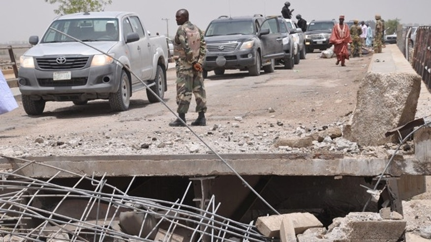 May 11, 2014: In this file photo, a soldier and government officials inspect the bridge that links Nigeria and Cameroon following an attack by Islamic militants in Gambaru, Nigeria.