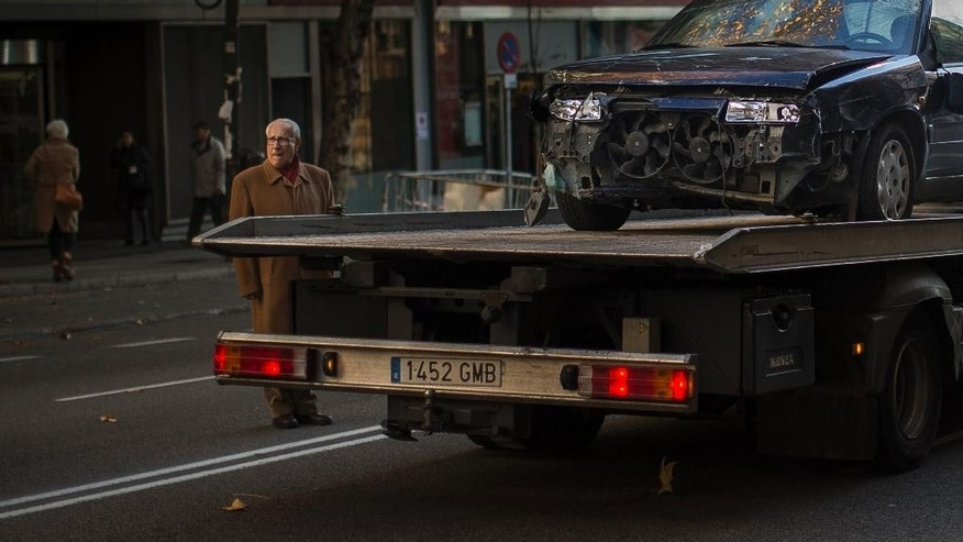 A truck removes a crashed car after a man rammed it into the headquarters of the ruling conservative Popular Party in Madrid, Spain, Friday, Dec. 19, 2014. Spanish police searched Friday for possible explosives at the Madrid headquarters of the ruling conservative Popular Party after a man rammed his car into the office entrance. No one was injured in the early-morning incident and National Police spokesman Antonio Nevado told Spanish National Radio that the attack did not appear to be terrorism-related. (AP Photo/Andres Kudacki)