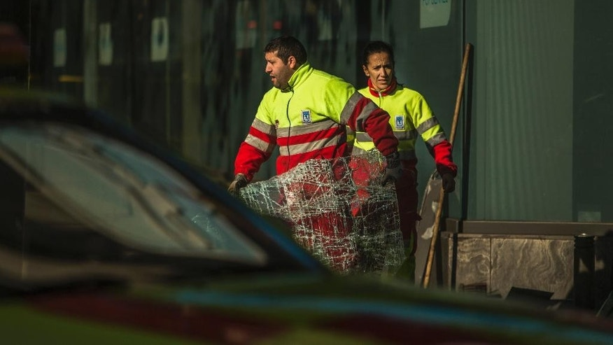 Workers clear up the area and remove broken glass after a man rammed his car into the headquarters of the ruling conservative Popular Party in Madrid, Spain, Friday, Dec. 19, 2014. Spanish police searched Friday for possible explosives at the Madrid headquarters of the ruling conservative Popular Party after a man rammed his car into the office entrance. No one was injured in the early-morning incident and National Police spokesman Antonio Nevado told Spanish National Radio that the attack did not appear to be terrorism-related. (AP Photo/Andres Kudacki)