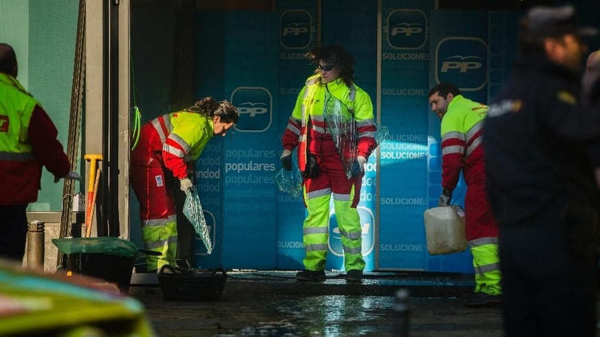 Workers clear up the area and removes broken glasses after a man rammed his car into the headquarters of the ruling conservative Popular Party in Madrid, Spain, Friday, Dec. 19, 2014. Spanish police searched Friday for possible explosives at the Madrid headquarters of the ruling conservative Popular Party after a man rammed his car into the office entrance. No one was injured in the early-morning incident and National Police spokesman Antonio Nevado told Spanish National Radio that the attack did not appear to be terrorism-related. (AP Photo/Andres Kudacki)