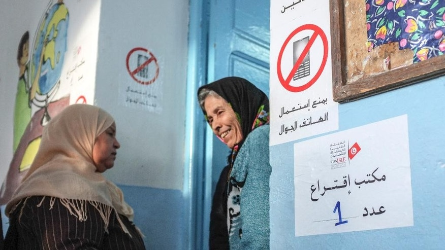 Women share a laugh in front of a polling station in Tunis, Tunisia, Sunday, Dec. 21, 2014.  Tunisians voted on Sunday for a new president in a runoff between a symbol of the country's previous regimes and a veteran human rights activist that came to power after the revolution of 2011.(AP Photo/Ilyess Osmane)