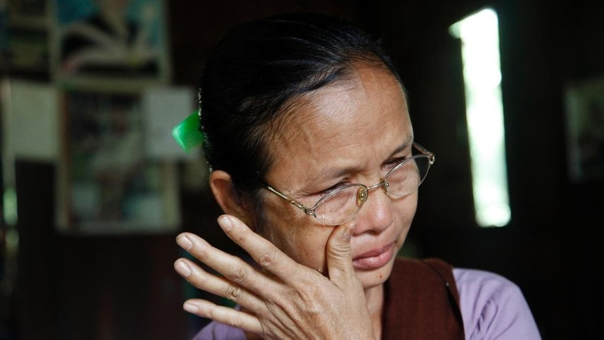 In this photo taken on Nov. 7, 2014, Aye Pu, mother of May Aye Nwe, 20, who was lost at sea during the Indian Ocean tsunami in 2004, wipes her tears during an interview at her home in Seint Paing, Myanmar. An Associated Press investigation helped track down two families with loved ones at the Tsunami Victims' Cemetery in southern Thailand, including Maye Aye Nwe's mother. As the 10th anniversary of the disaster approaches, Aye Pu, now a 55-year-old widow, says her healing process can finally begin. (AP Photo/Khin Maung Win)