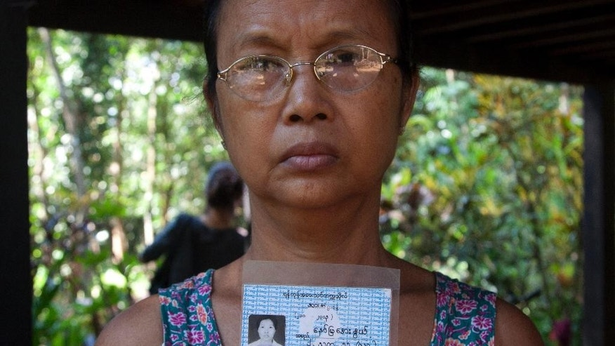 In this photo taken on Nov. 16, 2014, Aye Pu, mother of May Aye Nwe, 20, who was lost at sea during the Indian Ocean tsunami in 2004, holds up her daughter's student identification card during an interview at her home in Seint Paing, Myanmar. An Associated Press investigation helped track down two families with loved ones at the Tsunami Victims' Cemetery in southern Thailand, including Maye Aye Nwe's mother. As the 10th anniversary of the disaster approaches, Aye Pu, now a 55-year-old widow, says her healing process can finally begin. (AP Photo/Khin Maung Win)