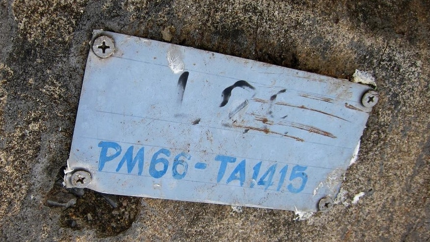 In this Nov. 27, 2014 photo, a metal plaque on a concrete stone serving as a headstone bears a reference number for May Aye Nwe, 20, from Myanmar, who died during the Indian Ocean tsunami in 2004, at the Tsunami Victims' Cemetery in Ban Bangmuang in Phang Nga province, Thailand. An Associated Press investigation helped track down two families with loved ones at the Tsunami Victims' Cemetery in southern Thailand. (AP Photo/Jerry Harmer)
