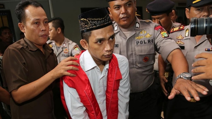 Police officers escort child sexual abuse suspect Zainal Abidin, center, before his trial at South Jakarta District Court in Jakarta, Indonesia, Monday, Dec. 22, 2014. An Indonesian court has sentenced five janitors to up to eight years in prison over the rape of a kindergartner at prestigious school in Indonesia. (AP Photo/Tatan Syuflana)