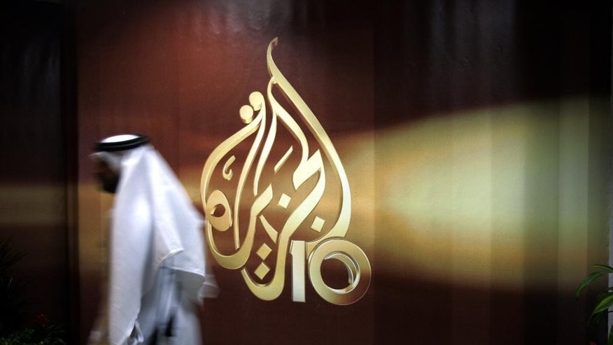 FILE - In this Wednesday Nov. 1, 2006 file photo, A Qatari employee of Al Jazeera Arabic language TV news channel passes by the logo of Al Jazeera in Doha, Qatar. The Doha-based Al-Jazeera satellite station has shut down its Egypt's channel which has been at the center of tense relations between the governments of Egypt's President Abdel-Fattah el-Sissi and Qatar. (AP Photo/Kamran Jebreili, File)