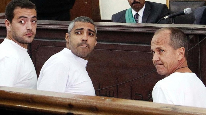 FILE - In this Monday, March 31, 2014 file photo, Al-Jazeera English producer Baher Mohamed, left, Canadian-Egyptian acting Cairo bureau chief Mohammed Fahmy, center, and correspondent Peter Greste, right, appear in court along with several other defendants during their trial on terror charges, in Cairo, Egypt. The Doha-based Al-Jazeera satellite station has shut down its Egypt's channel which has been at the center of tense relations between the governments of Egypt's President Abdel-Fattah el-Sissi and Qatar. (AP Photo/Heba Elkholy, El Shorouk, File) EGYPT OUT