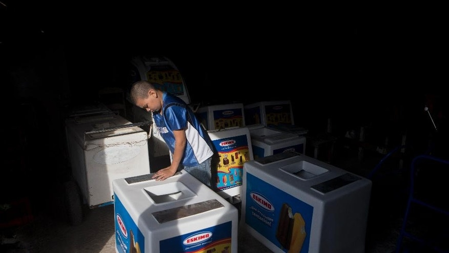 In this Tuesday, Nov. 25, 2014 photo, Roberto Castellanos assembles an ice cream cart at a bicycle repair ship in Tegucigalpa, Honduras. Wise beyond his years, Roberto says he knows that many people consider child labor to be exploitation, but he sees it as opportunity _ a means to survive the gang-controlled capital of a country with the world's highest homicide rate. (AP Photo/Esteban Felix)
