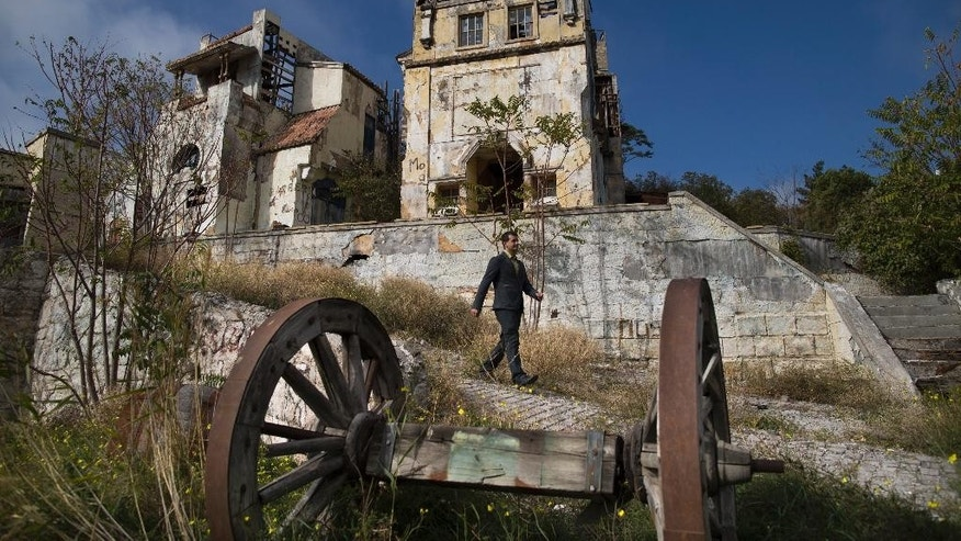 In this photo taken on Wednesday, Oct.  29, 2014, Andrei Nikolaev, manager of Yalta Film Studios, walks across one of the movie sets in the hills of Crimea.Yalta Film Studios is one of dozens of businesses to be forcibly taken over this year since Crimea's new pro-Moscow leaders came to power in March. (AP Photo/Alexander Zemlianichenko)