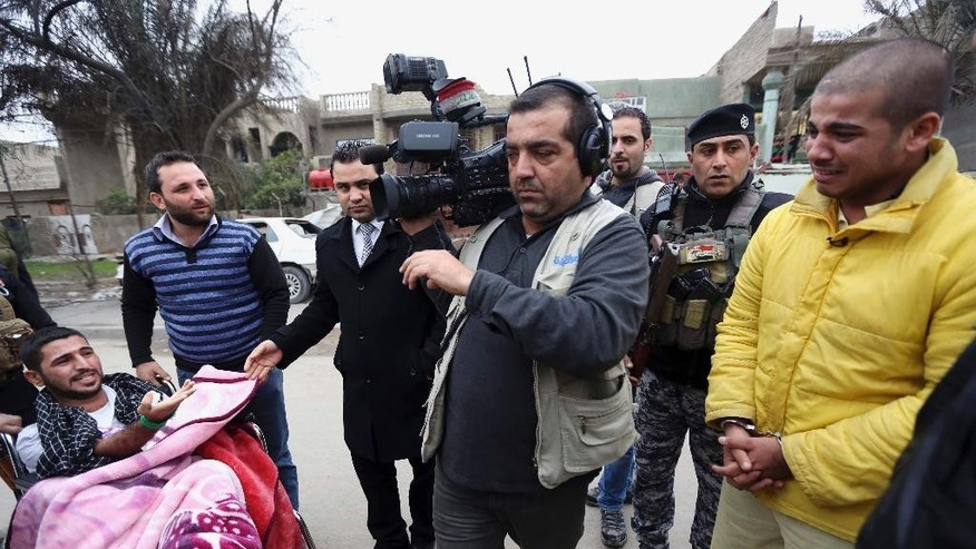 "In this photo taken Tuesday, Dec. 16, 2014, Haider Ali Motar, right, performs a scene from ""In the Grip of the Law,"" a reality show produced by Iraqi state TV, as a TV cameraman moves his position in Baghdad, Iraq. Motar was convicted of terrorism charges about a month ago for helping to carry out a string of Baghdad car bombings on behalf of the Islamic State extremist group. Now, the 21-year old is a reluctant cast member in the reality TV show. (AP Photo/Hadi Mizban)"