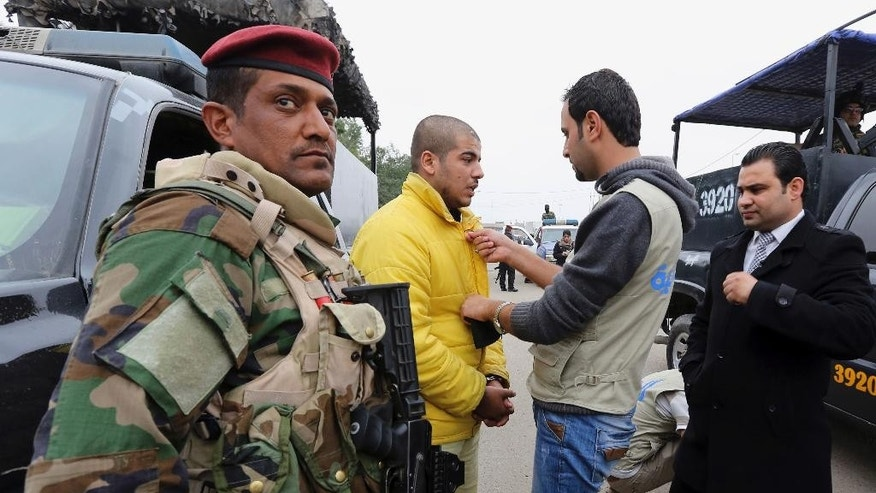 "In this photo taken Tuesday, Dec. 16, 2014, a TV crew member attaches a lavalier microphone on Haider Ali Motar's yellow prison costume, as Motar performs a scene from ""In the Grip of the Law,"" a reality show produced by Iraqi state TV, in Baghdad, Iraq. Motar was convicted of terrorism charges about a month ago for helping to carry out a string of Baghdad car bombings on behalf of the Islamic State extremist group. Now, the 21-year old is a reluctant cast member in the reality TV show. (AP Photo/Hadi Mizban)"