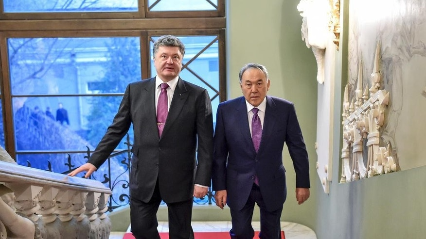 Ukrainian President Petro Poroshenko, left, and Kazakh President Nursultan Nazarbayev walk up the stairs in the Presidential office during their meeting in Kiev, Ukraine, Monday, Dec. 22, 2014. (AP Photo/Mykola Lazarenko, Pool)