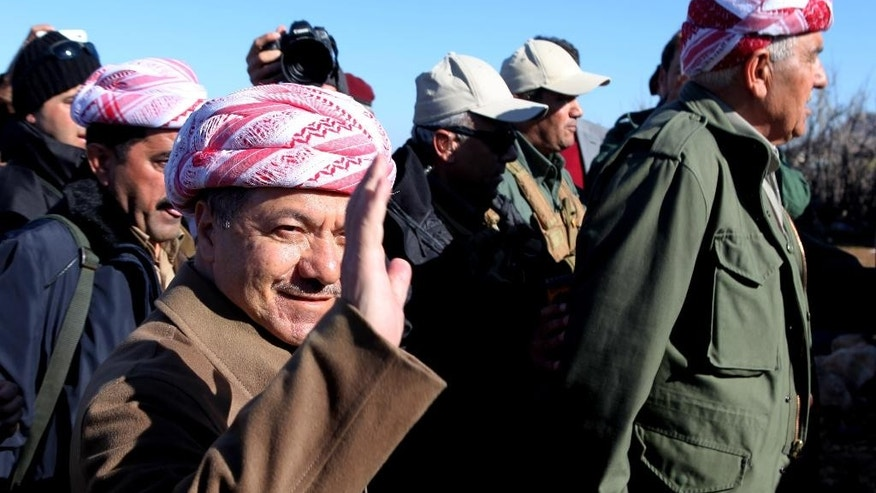 Kurdistan Iraqi regional government President Massoud Barzani arrives to support Kurdish forces as they head to battle Islamic State militants, on the summit of Mount Sinjar, in the town of Sinjar, Iraq, Sunday, Dec. 21, 2014. Iraqi Kurdish fighters pushed their way Sunday into the town of Sinjar, backed by U.S.-led coalition airstrikes against Islamic State militants who captured the town last summer. Loud explosions and intense gunbattles were heard from inside the town. Barzani vowed to crush the Islamic State group as fighting rages in Sinjar. (AP Photo/Zana Ahmed)