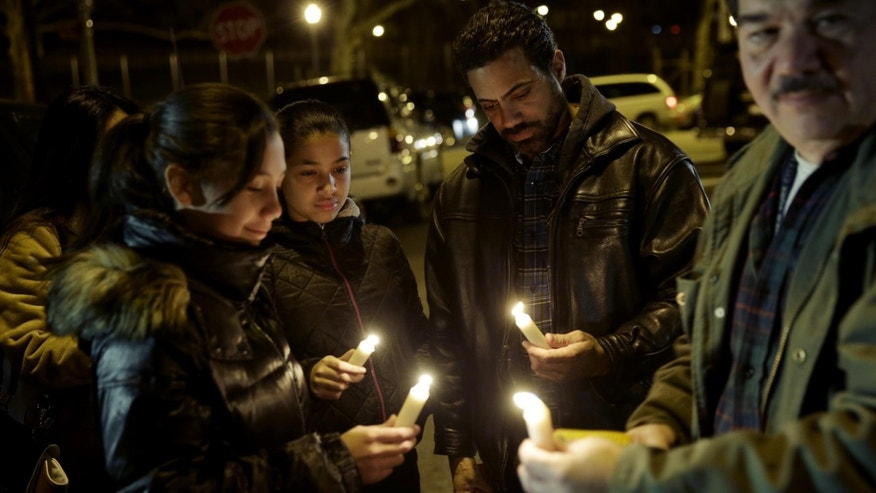 People light candles with members of Rafael Ramos' family in Brooklyn, New York, Sunday, Dec. 21, 2014.