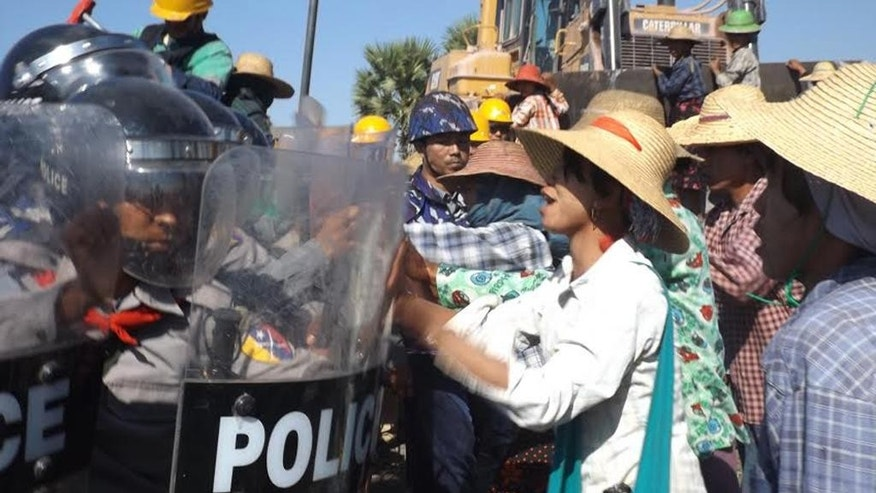 Farmers confront riot police at the site of the Letpadaung copper mine near Monywa in northwestern Myanmar Monday, Dec. 22, 2014. A woman was fatally shot Monday during a crackdown on protesters at the controversial Chinese-backed copper mine, activists and an opposition lawmaker said. Khin San Hlaing, a lawmaker from the National League for Democracy party, said the confrontation at the Letpadaung copper-mine project, a joint venture between a Myanmar military-controlled holding company and China's Wanbao Mining Copper Ltd., occurred as police and Chinese workers erected a fence on land that the villagers claimed as theirs. (AP Photo)