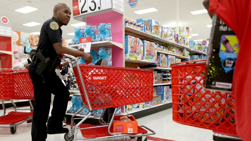 "MIAMI, FL - DECEMBER 19: City of Miami police officer, Earnest Lawrence, shops during the ""Shop with a Cop"" program that helps the Police Athletic League give gifts to children during the holiday season at a Target store on December 19, 2013 in Miami, Florida. Target announced that about 40 million credit and debit card accounts of customers who made purchases by swiping their cards at terminals in its U.S. stores between November 27 and December 15 may have been stolen.  (Photo by Joe Raedle/Getty Images)"