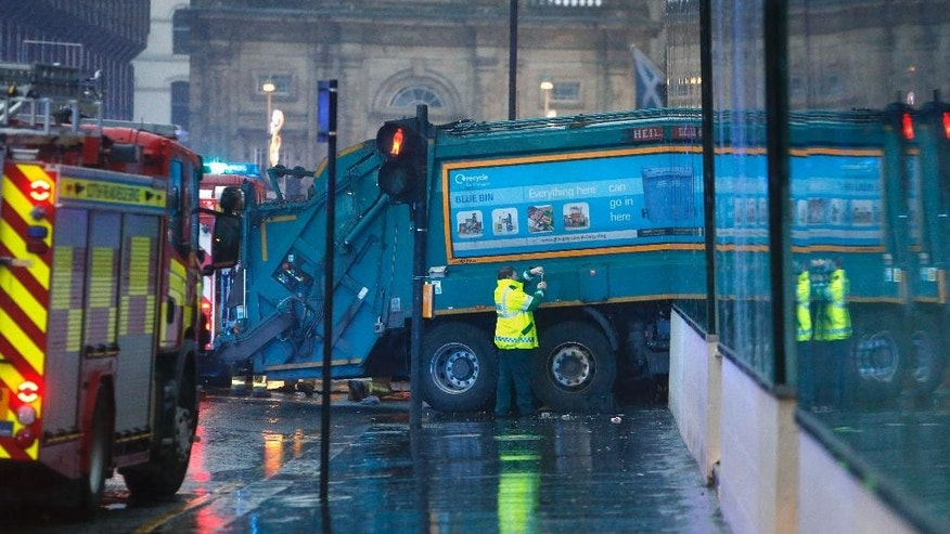 "The scene in George Square in Glasgow Scotland  after it is understood a garbage truck, rear right,  crashed into a group of pedestrians Monday Dec. 22, 2014. Police say an ""ongoing serious incident"" is unfolding in the city centre of Glasgow in Scotland. Emergency services responded Monday to reports that a truck has crashed into a group of pedestrians. The incident happened near George Square in the central part of the city. Surrounding roads have been closed. Police weren't immediately able to give further details about the situation. (AP Photo/Danny Lawson/PA) UNITED KINGDOM OUT"