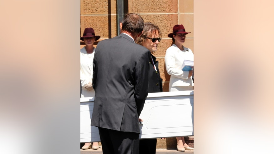 Ken Johnson, center back, carries the coffin of his son Tori during a funeral service in Sydney, Australia, Tuesday, Dec. 23, 2014. Tori Johnson was one of three people including the gunman who were killed during a siege in the Lindt cafe coffee shop in Sydney on Tuesday morning Dec. 16, 2014. (AP Photo/Rob Griffith)