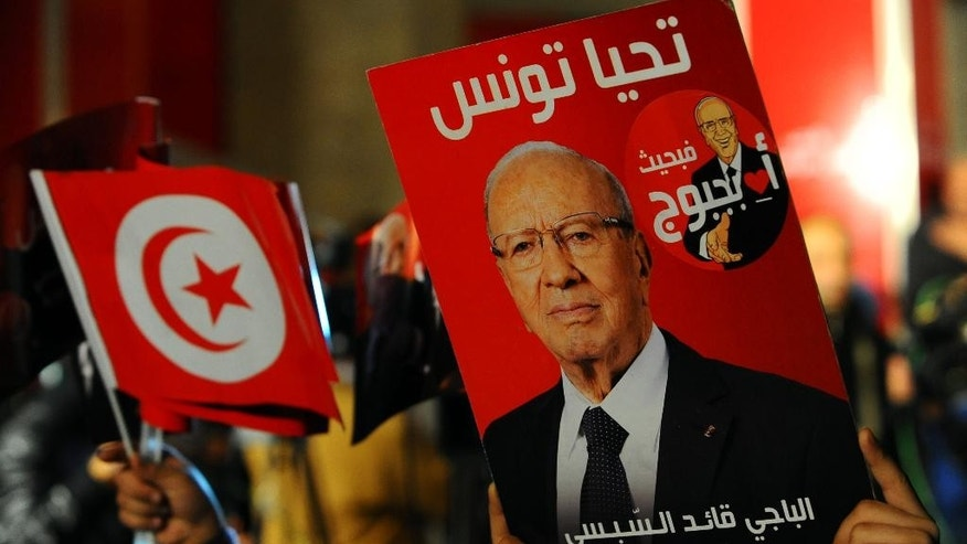 A supporter holds a poster of Tunisian presidential candidate Beji Caid Essebsi as he celebrates after the first results following the second round of the country's presidential election, in Tunis, Sunday, Dec. 21, 2014. Tunisian polling firms have declared Beji Caid Essebsi, an 88-year-old official from previous regimes, as the winner of Sunday's presidential runoff, cementing his dominance over a country where his party already controls Parliament. (AP Photos/Hassene Dridi)